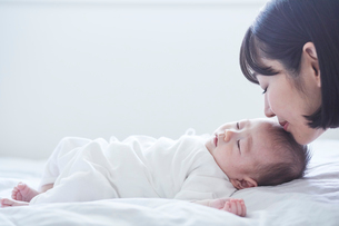 寝る赤ちゃんと見守る母親の写真素材 [FYI01802639]