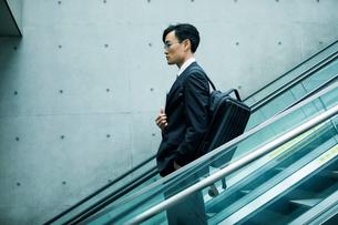 タブレットPCを持ちエスカレーターに乗るビジネスマンの写真素材 [FYI01802640]