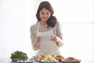 料理の写真を撮る女性の写真素材 [FYI01802666]