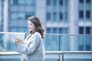 オフィス街でスマートフォンを持つ女性の写真素材 [FYI01802678]