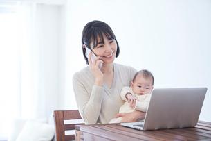 ノートパソコンを見る女性と赤ちゃんの写真素材 [FYI01802688]