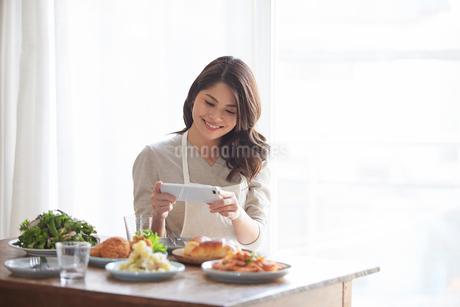 料理の写真を撮る女性の写真素材 [FYI01802698]
