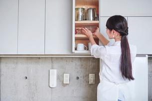 食器棚と女性の写真素材 [FYI01802703]