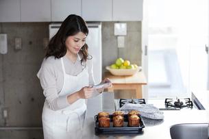 キッチンに立ち写真を撮る女性の写真素材 [FYI01802709]