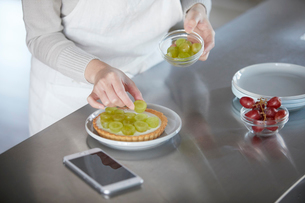 スマートフォンを見ながらケーキを作る女性の写真素材 [FYI01802730]