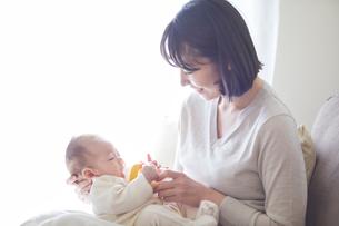 赤ちゃんを抱っこする母親とミルクを飲む赤ちゃんの写真素材 [FYI01802731]