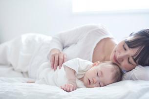 眠る赤ちゃんと添い寝をする母親の写真素材 [FYI01802733]