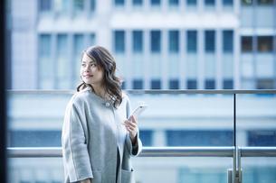 オフィス街でスマートフォンを持つ女性の写真素材 [FYI01802747]