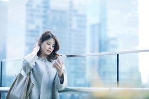 オフィス街でスマートフォンを持つ女性の写真素材 [FYI01802758]