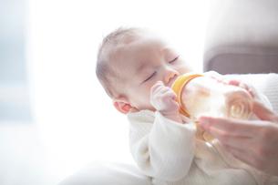 赤ちゃんを抱っこする母親とミルクを飲む赤ちゃんの写真素材 [FYI01802760]