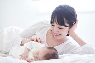 眠る赤ちゃんと添い寝をする母親の写真素材 [FYI01802762]