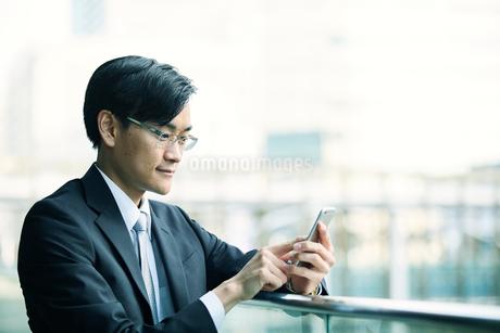 スマートフォンをもつビジネスマンの写真素材 [FYI01802765]