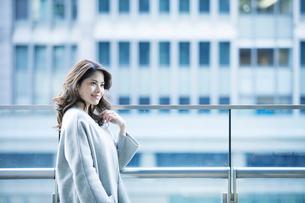 オフィス街でスマートフォンを持つ女性の写真素材 [FYI01802768]