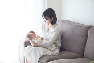 赤ちゃんを抱っこする母親とミルクを飲む赤ちゃんの写真素材 [FYI01802769]