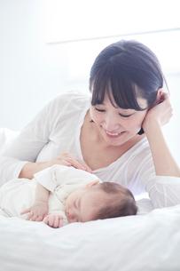 眠る赤ちゃんと添い寝をする母親の写真素材 [FYI01802770]
