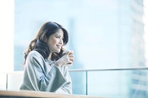 カフェでコーヒーカップとタブレットPCを持つ女性の写真素材 [FYI01802772]