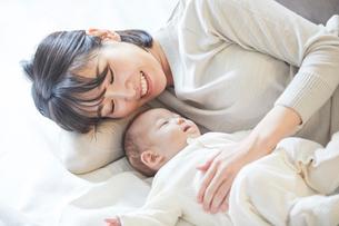 眠る赤ちゃんと添い寝をする母親の写真素材 [FYI01802774]