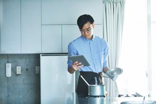 キッチンに立ち料理を作る男性の写真素材 [FYI01802789]