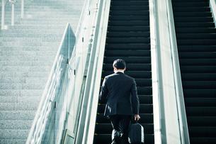 エスカレーターに乗るビジネスマンの写真素材 [FYI01802796]