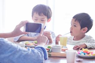 料理を食べる男の子をスマートフォンで撮影する女性の写真素材 [FYI01802809]
