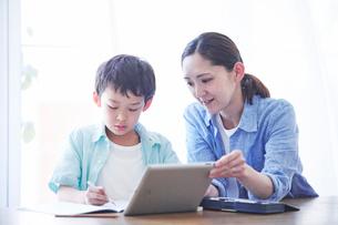 ペンを持つ男の子とタブレット端末を持つ母親の写真素材 [FYI01802834]