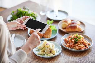料理の写真を撮る女性の写真素材 [FYI01802851]