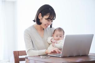 ノートパソコンを見る女性と赤ちゃんの写真素材 [FYI01802860]