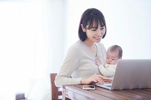 ノートパソコンを見る女性と赤ちゃんの写真素材 [FYI01802863]