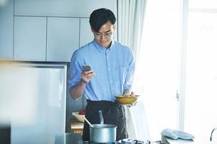 キッチンに立ち料理を作る男性の写真素材 [FYI01802865]