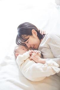 眠る赤ちゃんと添い寝をする母親の写真素材 [FYI01802884]