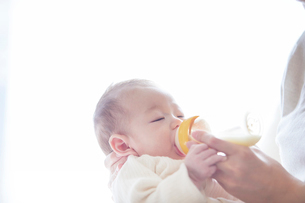 赤ちゃんを抱っこする母親とミルクを飲む赤ちゃんの写真素材 [FYI01802888]