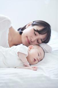 眠る赤ちゃんと添い寝をする母親の写真素材 [FYI01802897]