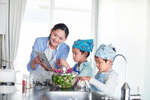 キッチンで料理を作る男の子と女性の写真素材 [FYI01802919]