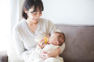 赤ちゃんを抱っこする母親とミルクを飲む赤ちゃんの写真素材 [FYI01802923]