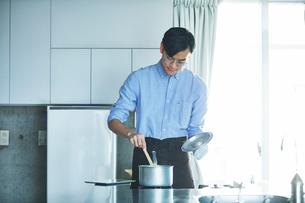 キッチンに立ち料理を作る男性の写真素材 [FYI01802928]