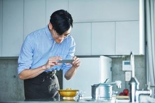 キッチンに立ちスマートフォンで料理の写真を撮る男性の写真素材 [FYI01802939]