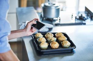キッチンに立ちスマートフォンでマフィンの写真を撮る男性の写真素材 [FYI01802975]