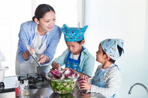 キッチンで料理を作る男の子と女性の写真素材 [FYI01803007]