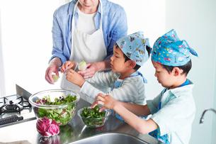 キッチンで料理を作る男の子と女性の写真素材 [FYI01803025]