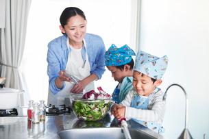 キッチンで料理を作る男の子と女性の写真素材 [FYI01803043]