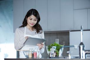 タブレットPCを持ち料理を作る女性の写真素材 [FYI01803108]