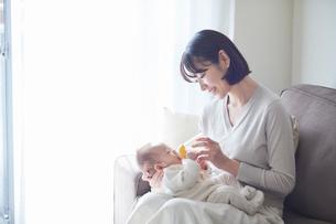 赤ちゃんを抱っこする母親とミルクを飲む赤ちゃんの写真素材 [FYI01803133]