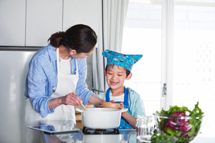 キッチンで料理を作る男の子と女性の写真素材 [FYI01803148]