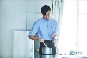 キッチンに立ち料理を作る男性の写真素材 [FYI01803150]