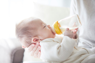 赤ちゃんを抱っこする母親とミルクを飲む赤ちゃんの写真素材 [FYI01803153]