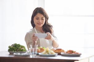料理の写真を撮る女性の写真素材 [FYI01803170]