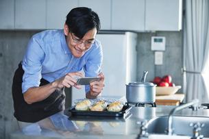キッチンに立ちスマートフォンでマフィンの写真を撮る男性の写真素材 [FYI01803175]