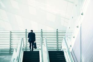 エスカレーターに乗るビジネスマンの写真素材 [FYI01803176]
