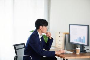 パソコンに向かい働くビジネスマンの写真素材 [FYI01803177]