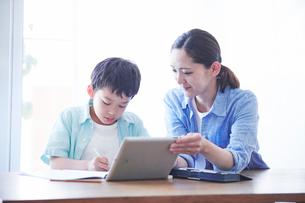 ペンを持つ男の子とタブレット端末を持つ母親の写真素材 [FYI01803194]